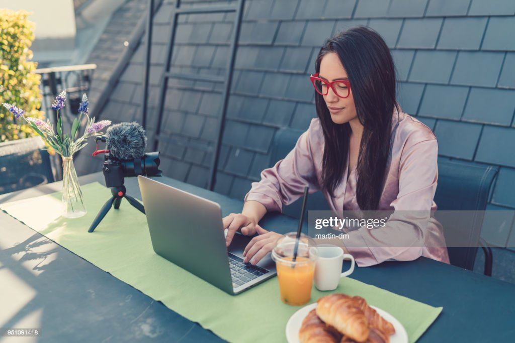Freelancer vlogging from rooftop terrace : Stock Photo