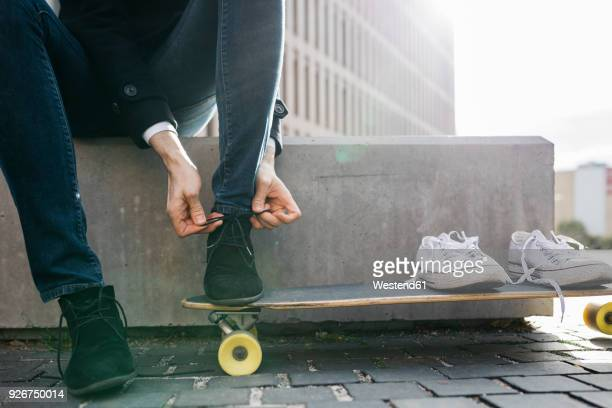 freelancer with longboard sitting on bench tying his shoes, partial view - work shoe stock-fotos und bilder