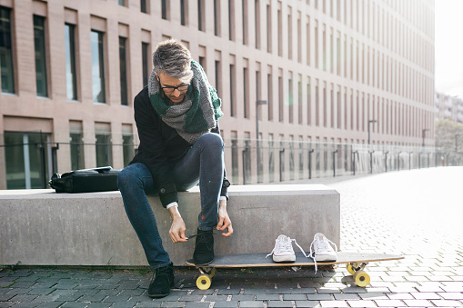 Freelancer with longboard sitting on bench tying his shoes - gettyimageskorea