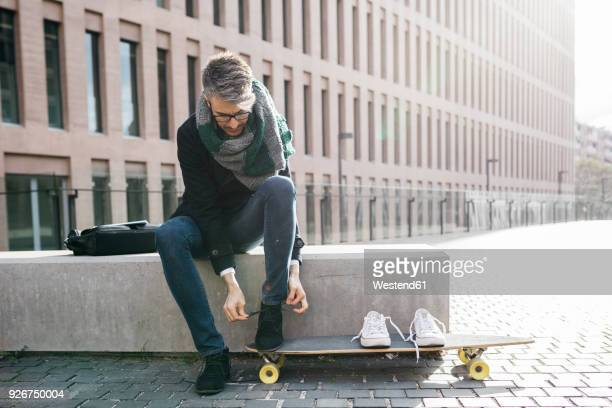 freelancer with longboard sitting on bench tying his shoes - longboard skating stock pictures, royalty-free photos & images