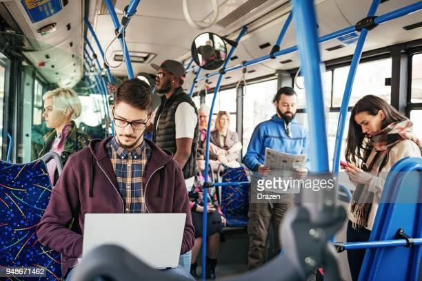 freelancer working on laptop in public bus - hora de ponta papel humano imagens e fotografias de stock