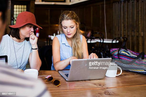 Freelancers using laptop while working at cafe table