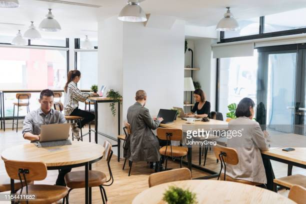 freelancers working on computers in modern coworking space - hot desking stock pictures, royalty-free photos & images