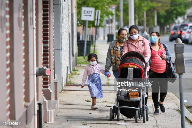 Group of mothers and children walk down Church St. In Freeport, New York wearing face masks on May 19 during the coronavirus pandemic. ,