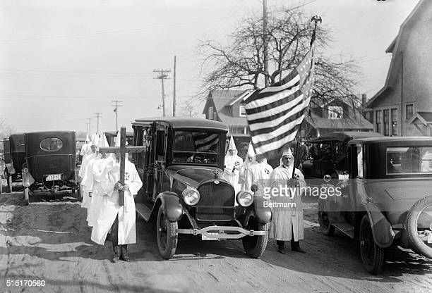 Robed Ku Klux Klansmen accompanying the hearse of one of their members Undated photograph