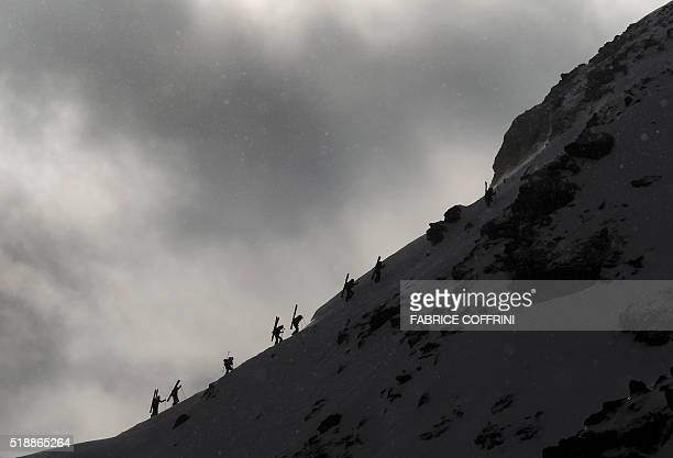 Freeriders climb a windswept Bec des Rosses mountain to compete for the men's ski event at the Verbier Xtreme Freeride World Tour final on April 3...