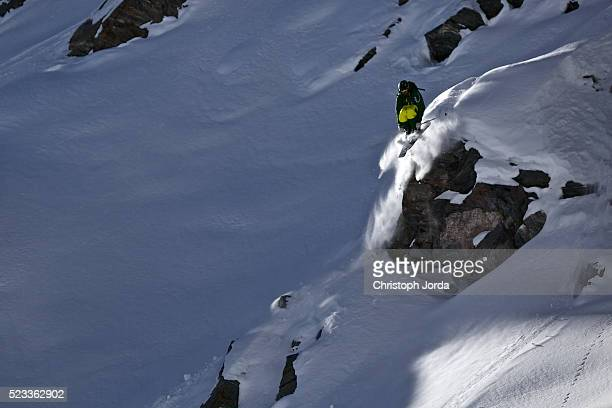 Freeskier jumping over cliff of mountain, Switzerland, Alps
