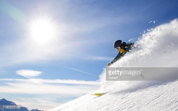 freifahrende, die abseits der piste fahren und frischen pulverschnee in einem schönen wintertag versprühen - schneebedeckt stock-fotos und bilder