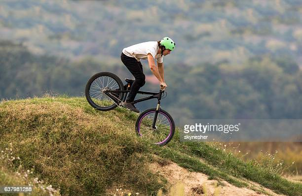 Freestyle cyclist riding down the hill in nature.