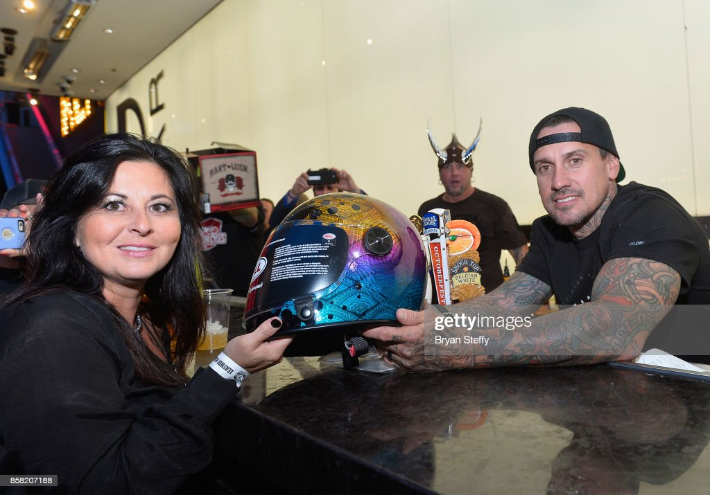 Freestyle motocross rider Carey Hart (R) presents a guest with a custom painted helmet as he surprises guests as a bartender in support of Carey Hart's Good Ride Rally benefiting Infinite Hero Foundation at The D Bar, D Las Vegas on October 5, 2017 in Las Vegas, Nevada.