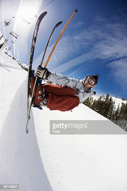freestyle skier grabbing edge in halfpipe - スキージャンプ ストックフォトと画像