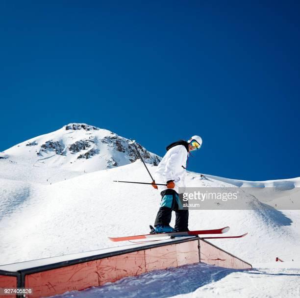 Skieur acrobatique de meulage sur rail en snowpark