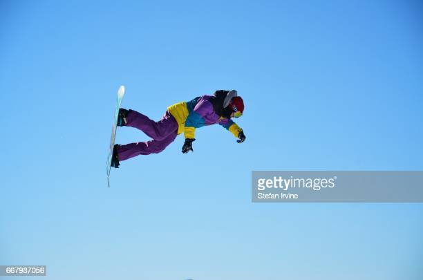 A freestyle snowboarder performs an aerial trick as he launches from a jump in Les Arcs France