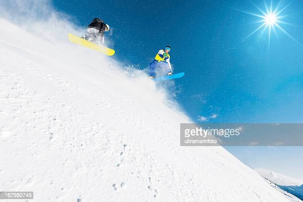 Freestyle snowboarders in a jump