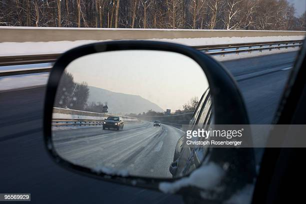 Freeway and snow in rearview mirror