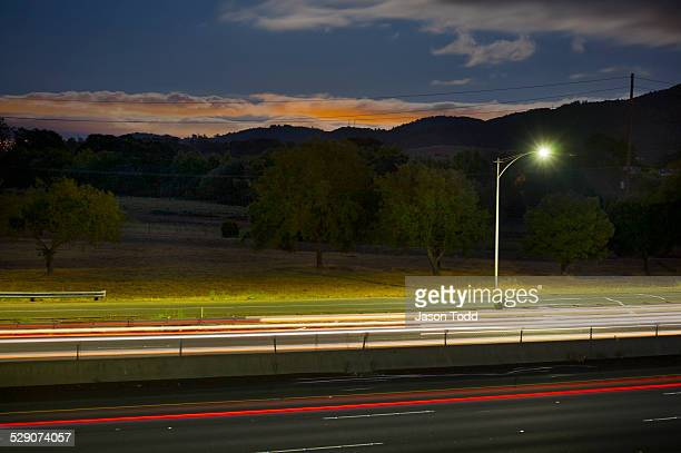 freeway, car lights with street light at dusk - jason todd stock photos and pictures
