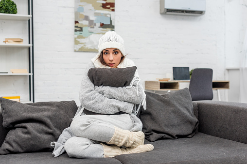 freezed young woman in warm clothes sitting on couch and hugging cushion at home 1062148914