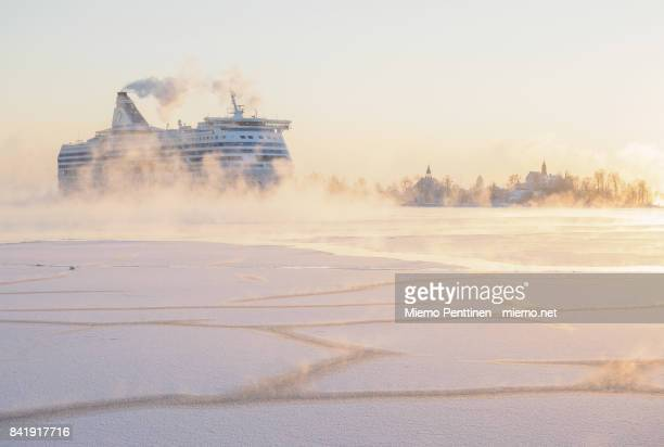 A freezing winter morning in Helsinki: huge ferry coming to the harbor through the mist rising from the frozen sea