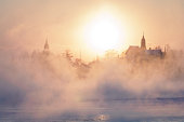 A freezing winter morning in Helsinki: sun coming up behind the mist rising from the frozen sea