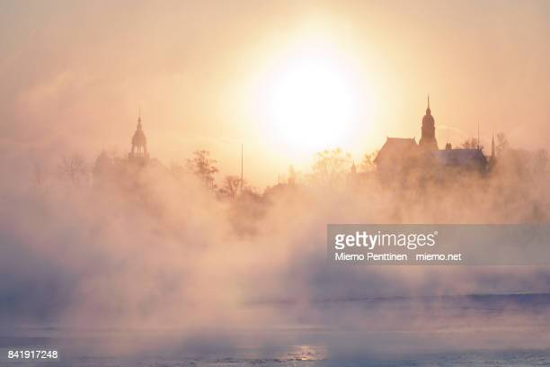 a freezing winter morning in helsinki: sun coming up behind the mist rising from the frozen sea - helsinki stockfoto's en -beelden