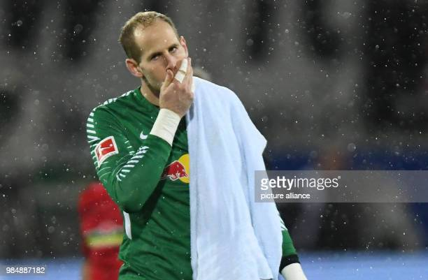 SC Freiburg and RB Leipzig face off in a Bundesliga match at Freiburg/Breisgau Germany 20 January 2018 Leipzig's goalkeeper Peter Gulacsi wipes his...