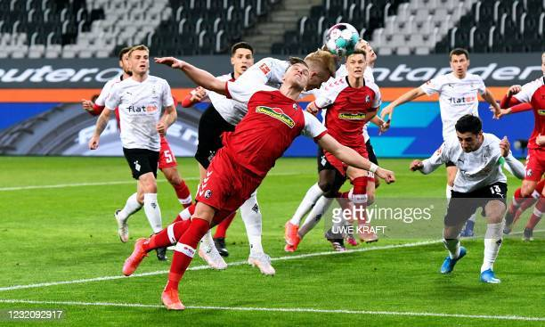 Freiburg's Bosnian forward Ermedin Demirovic and Moenchengladbach's Swedish defender Oscar Wendt both go to head the ball during the German first...