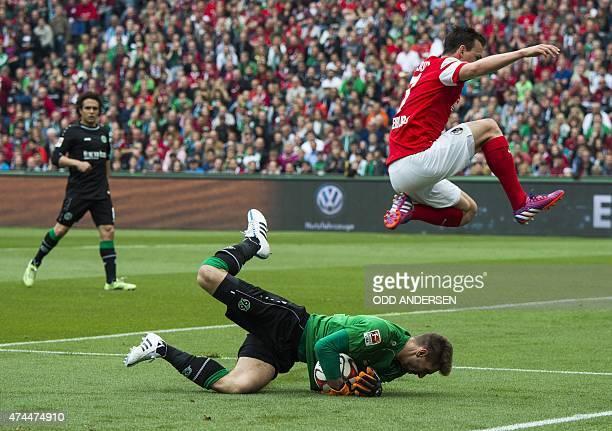 Freiburg's Czech defender Vladimir Darida jumps over Hannover goalkeeper RonRobert Zieler making a save during German first division Bundesliga...
