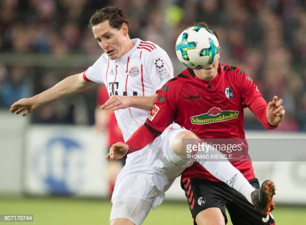 Freiburg's defender Christian Guenter and Munich's midfielder Sebastian Rudy vie with the ball during the German first division Bundesliga football...