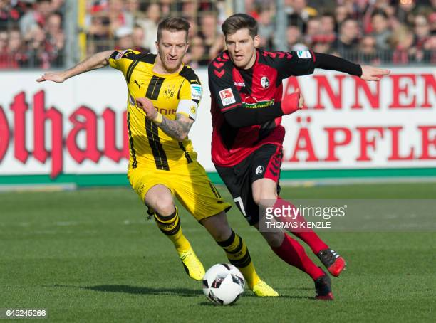 TOPSHOT Freiburg's defender Lukas Kuebler and Dortmund's midfielder Marco Reus vie for the ball during the first German division Bundesliga football...