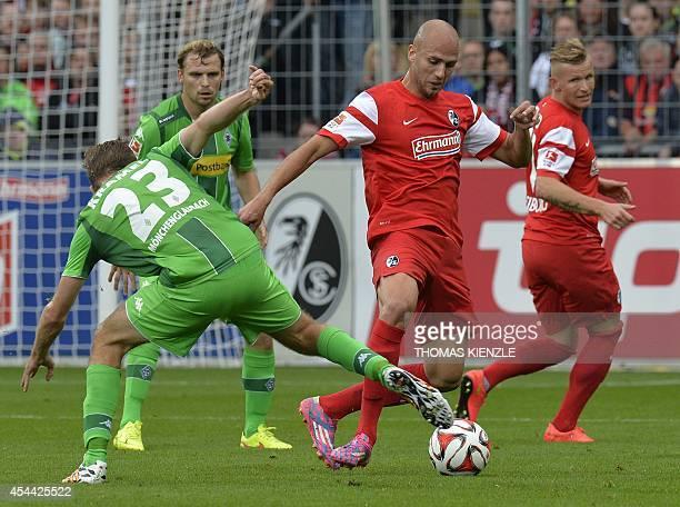 Freiburg's forward Dani Schahin and Moenchengladbach's midfielder Christoph Kramer vie for the ball during the German first division Bundesliga...