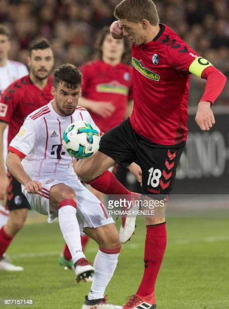 Freiburg's forward Nils Petersen and Munich's Spanish defender Juan Bernat vie with the ball during the German first division Bundesliga football...