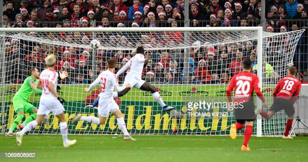 Freiburg's forward Nils Petersen scores the 10 past Leipzig's Hungarian goalkeeper Peter Gulacsi during the German first division Bundesliga football...