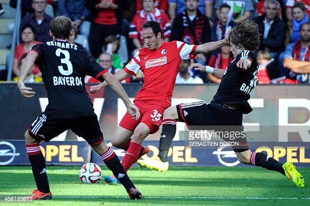 Freiburg's forward Sebastian Freis vies with Leverkusen's midfielder Stefan Reinartz and Leverkusen's Croatian defender Tin Jedvaj during the German...