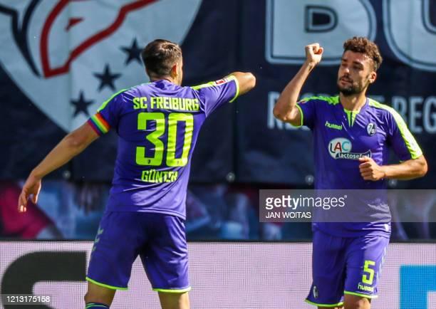 Freiburg's German defender Manuel Gulde celebrates scoring the opening goal with Freiburg's German defender Christian Guenter during the German first...