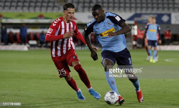 Freiburg's German defender Robin Koch and Moenchengladbach's French forward Marcus Thuram vie for the ball during the German first division...