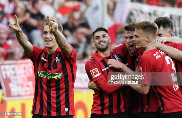 Freiburg's German forward Nils Petersen celebrates with teammates after he scored the 2-0 during the German First division Bundesliga football match...