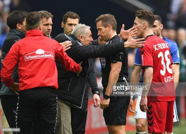 Freiburg's German head coach Christian Streich debates with referee Tobias Stieler during the German first division Bundesliga football match FC...