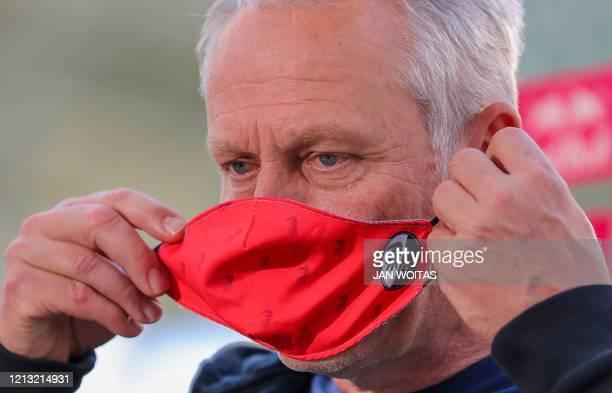 Freiburg's German head coach Christian Streich takes off his face mask to give an interview after the German first division Bundesliga football match...