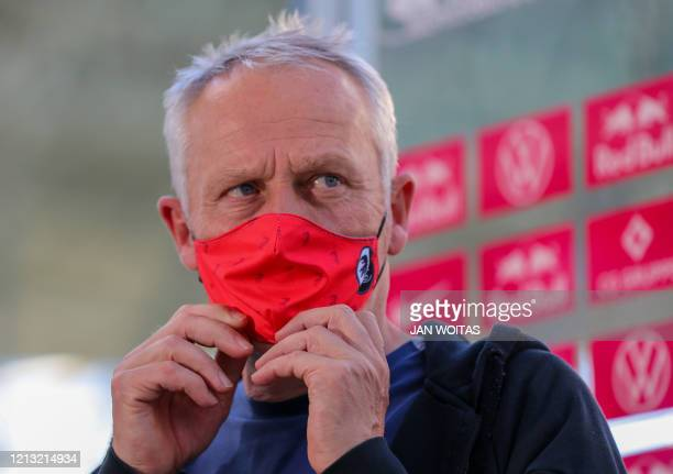 Freiburg's German head coach Christian Streich wears a face mask as he prepares to give an interview after the German first division Bundesliga...