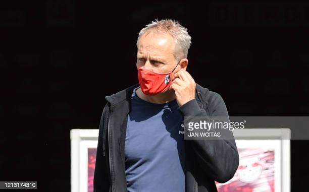 Freiburg's German head coach Christian Streich wears a face mask during the German first division Bundesliga football match RB Leipzig v SC Freiburg...