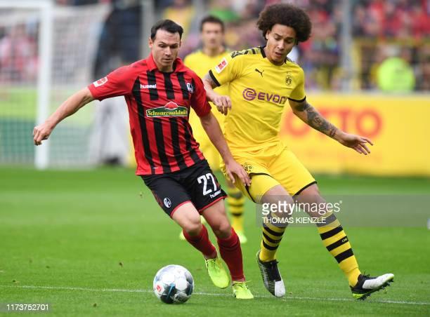 Freiburg's German midfielder Nicolas Hoefler and Dortmund's Belgian midfielder Axel Witsel vie for the ball during the German first division...