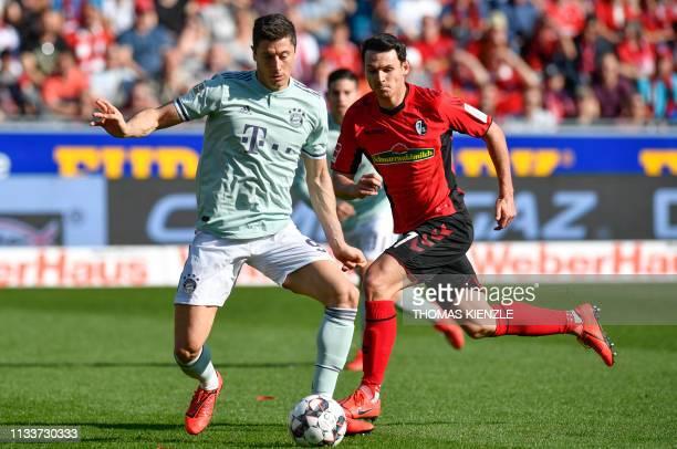 Freiburg's German midfielder Nicolas Hoefler and Munich's Polish forward Robert Lewandowski vie for the ball during the German first division...