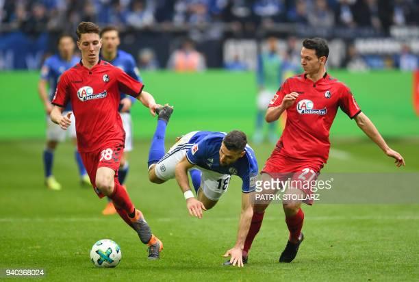 TOPSHOT Freiburg's German midfielder Nicolas Hoefler Freiburg's German defender Florian Kath and Schalke's German midfielder Daniel Caligiuri vie for...