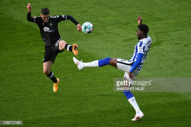 Freiburg's Hungarian midfielder Roland Sallai and Hertha Berlin's German defender Jordan Torunarigha vie for the ball during the German first...