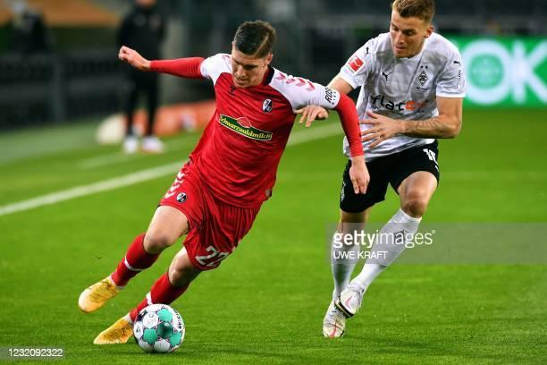 Freiburg's Hungarian midfielder Roland Sallai and Moenchengladbach's German defender Louis Jordan Beyer vie for the ball during the German first...