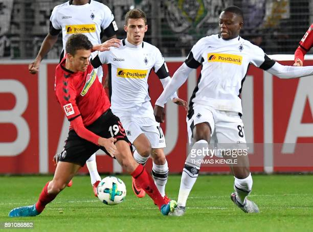 Freiburg's midfielder Janik Haberer Moenchengladbach's Belgian forward Thorgan Hazard and Swiss midfielder Denis Zakaria vie for the ball during the...