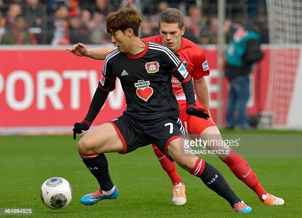 Freiburg's midfielder Matthias Ginter and Leverkusen's Korean forward Heung Min Son vie for the ball during the German first division Bundesliga...