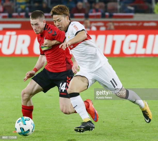 Freiburg's Ryan Kent tries to fend off the challenge of Takuma Asano of Stuttgart during the second half of a German Bundesliga match at MercedesBenz...