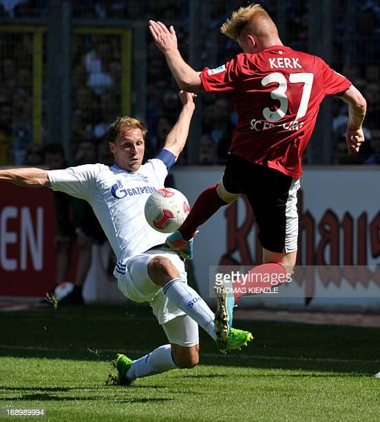 Freiburg's Sebastian Kerk vies for the ball with Schalke's defender Benedikt Hoewedes during the German first division Bundesliga football match SC...