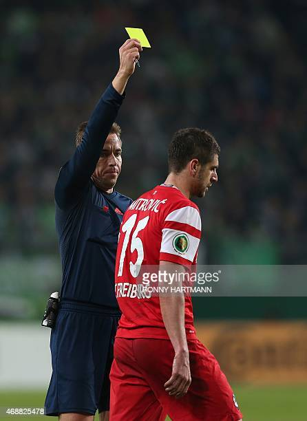 Freiburg's Serbian defender Stefan Mitrovic is shown a yellow card during the German Football Cup DFB Pokal quarterfinal football match between VfL...